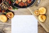 Saffron milk cap mushrooms on wooden table. Blank sheet of paper — Stock Photo