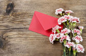 Red and white carnations and red envelope isolated on wood — Stock Photo