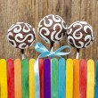 Chocolate cake pops and colorful rainbow fence on wooden back — Stock Photo #38643323
