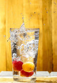 Water splash over glass. Apricot drink on hot summer day — Stock Photo