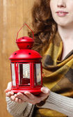 Woman holding red christmas lantern. Wooden wall in the back — Stok fotoğraf