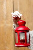 Woman holding red christmas lantern. Wooden wall in the back — Stockfoto