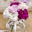 Bouquet of carnation flowers in glass vase on wooden table. Gold — Stock Photo