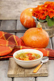 Bowl of tomato and pepper soup on wooden table. Autumn setting. — Stock Photo