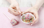 Decorating cake pops with colorful sprinkles — Stock Photo
