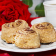 Cinnamon rolls on white plate among rose petals — Stock Photo #38936767