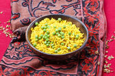 Indian cuisine: bowl of yellow rice with green peas on red backg — Stock Photo