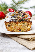 Fruitcake with dried fruits and nuts in christmas setting — Stock Photo