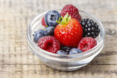 Fruit salad in small transparent bowl on wooden table — Stock Photo