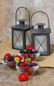 Fruit salad in small bowls on wooden table. Black iron lanterns — Stock Photo
