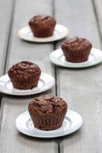Chocolate muffins before decorating on wooden table — Stock Photo