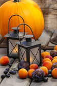 Autumn fruits and traditional lanterns on wooden table — Stock Photo