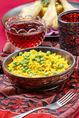 Indian cuisine: bowl of yellow rice with green peas on red — Stock Photo