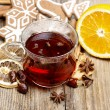 Glass of hot steaming teamong christmas decorations on wooden — Stock Photo #39073111