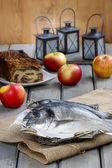 Gilt-head bream fishes in wicker basket on wooden table. — Stock Photo