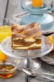 Piece of toffee and vanilla cake on transparent glass cake stand — Stock Photo