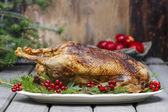 Baked goose on wooden table. Popular christmas dish — Stock Photo