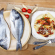 Gilt-head bream fish and penne with dried tomatoes on wood — Stock Photo