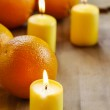 Beautiful candles and juicy oranges on wooden table — Stock Photo #39139753