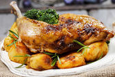 Roasted chicken with vegetables on wooden table — Stock Photo