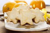 Christmas biscuits in star shape. Fresh oranges and candles — Stock Photo