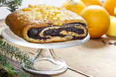 Poppy seed cake on glass cake stand under fir branch — Stock Photo