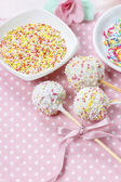 White cake pops on pink dotted table cloth. Colorful sprinkles — Stock Photo