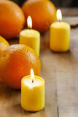 Beautiful candles and juicy oranges on wooden table — Stock Photo