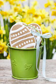 Easter gingerbread cookies in green bucket on wooden table — Stock Photo