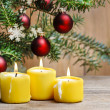 Yellow candles in front of christmas tree. — Stock Photo #39217297