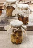 Pickled mushrooms in transparent glass jar — Stock Photo