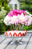 Strawberry cake on rustic wooden table in lush summer garden — Stock Photo