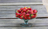 Glass bowl of fresh ripe strawberries on rustic wooden table. — Stock Photo