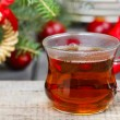 Stock Photo: Glass of hot steaming teamong christmas decorations. Copy spac