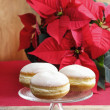 Stock Photo: Donuts on cake stand. Christmas setting, poinsettiin backg