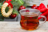 Glass of hot steaming tea among christmas decorations. Copy spac — Stock Photo