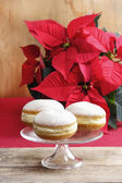 Donuts on cake stand. Christmas setting, poinsettia in the backg — Stock Photo