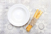 Empty bowl and traditional italian breadsticks on beautiful lace — Stock Photo