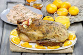 Roasted duck with oranges on wooden table — Stock Photo