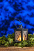 Beautiful lantern on fir branches, snowy night in the background — Stock Photo