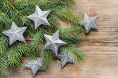 Shiny silver stars on fir branch. Wooden background, copy space — Stock Photo