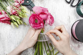 Florist at work. Woman making beautiful bouquet of pink persian  — Stock Photo