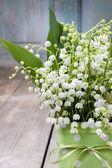 Bouquet of lily of the valley flowers in green dotted can — Stock Photo