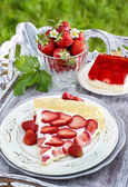 Strawberry cake on wooden tray in summer garden — Stock Photo