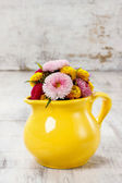 Bouquet of wild flowers in yellow jug, copy space — Stock Photo