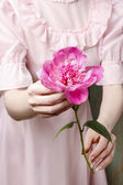 Woman in pink dress holding stunning pink peony — Stock Photo