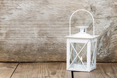 Simple white lantern on wooden background — Stock Photo