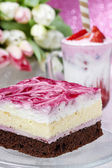 Layer cake with pink icing. Cup of strawberry milkshake — Stock Photo