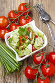 Bowl of fresh salad on rustic wooden table — Stock Photo