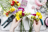 Florist at work. Woman making bouquet of freesia flowers — Foto Stock